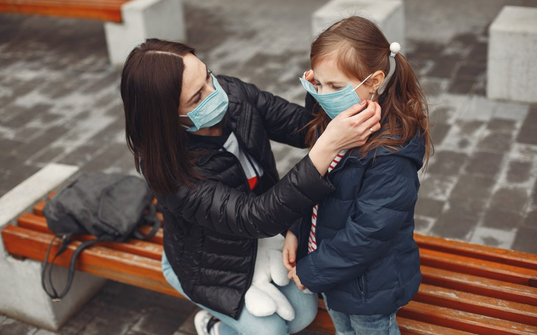 Woman in a disposable mask is teaching her child to wear a respirator